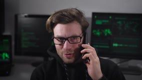 Profissional de TI novo que fala em seu telefone celular contra os computadores de um fundo que trabalham com E-informação em peq video estoque