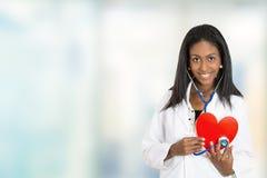 Profissional médico do doutor fêmea seguro que guarda o coração vermelho fotografia de stock