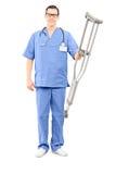 Profissional masculino dos cuidados médicos que guarda um par de muletas Imagens de Stock Royalty Free