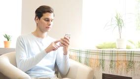 Profissional urbano novo do homem de negócios na mensagem texting dos sms do smartphone imagem de stock royalty free
