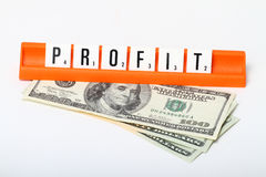 Profit. The word profit,spelled with scrabble letters, on top of some us dollars. on a white background royalty free stock photo