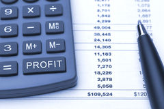 Profit button on calculator, pen and report. Macro blue calculator with additional button to calculate profit, column with different numbers and total earnings Royalty Free Stock Photography
