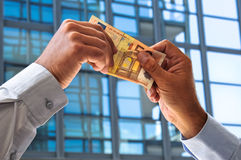 Profit in euro. Two hands exchanging a € 50 bill as a symbol of income Stock Image