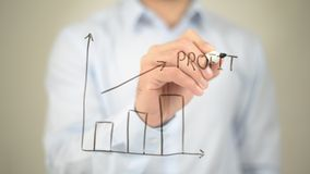Profit Graph,  Man writing on transparent screen Royalty Free Stock Image