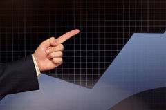 Profit growth. Finger showing the growth of profit over black graph Royalty Free Stock Image