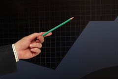 Profit growth. Pencil showing the growth of  profit over black graph Royalty Free Stock Photos
