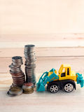 Profit growth concept truck toy with coin towers Stock Photos