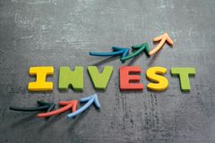 Profit or growth from investment concept, arrows pointing up as chart with colorful letters building the word INVEST on loft. Cement dark blackboard wall stock photography