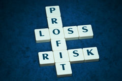 Profit, loss and risk crossword. On beautiful blue backround stock photo