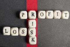 Profit, loss and risk crossword blocks on table. Top view Stock Photos