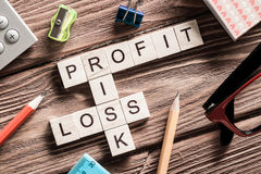 Profit loss and risk words on workplace collected of wooden cubes Stock Image