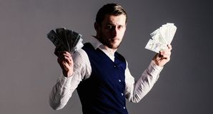 Profit and richness concept. Man in waistcoat, businessman, entrepreneur. Holding lot of money in both hands, grey background. Rich man, successful entrepreneur stock photos