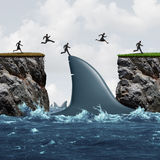 Profit From Risk. Business concept as a group of businesspeople taking advantage of challenging market conditions as a businessman and businesswoman jumping on Stock Image