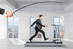 Profit-seeking concept with businessman running on a treadmill f. Or a bag of money hanging on a fishing tackle Stock Photo