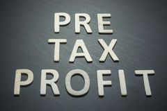 Profit before taxes written with wooden letters on a black backg. Round to understand a concept of economics and finance Royalty Free Stock Photos