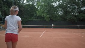 Profitennis, Paar des aktiven Teenagers spielen das Tennis und Ball, die über Netz auf rotem Gericht unter Regen sich werfen stock video footage