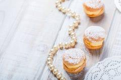 Profiterole или торты cream слойки заполненные с взбитой сливк на деревянном конце предпосылки вверх Очень вкусный десерт с оформ Стоковые Фото