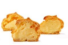 Profiterole eller eclair, hemlagade sötsaker, närbild som isoleras på vit bakgrund arkivbild