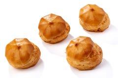 Profiterole eller eclair, hemlagade sötsaker, närbild som isoleras på vit bakgrund arkivfoton