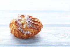 Profiterole. Homemade profiterole with cream on white wooden table Stock Photo
