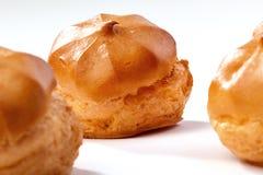 Profiterole o eclair, dulces hechos en casa, primer, aislado en el fondo blanco imagenes de archivo