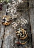 Profiteroles που βερνικώνεται στη σοκολάτα και που ψεκάζεται με τα ξέσματα ξύλων καρυδιάς Ξύλινη ανασκόπηση Κινηματογράφηση σε πρ Στοκ Φωτογραφία