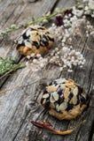 Profiteroles που βερνικώνεται στη σοκολάτα και που ψεκάζεται με τα ξέσματα ξύλων καρυδιάς Ξύλινη ανασκόπηση Κινηματογράφηση σε πρ Στοκ φωτογραφία με δικαίωμα ελεύθερης χρήσης