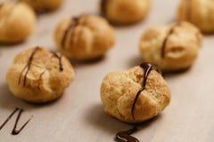 Profiteroles που διακοσμείται με τη σκοτεινή σοκολάτα στην κινηματογράφηση σε πρώτο πλάνο καφετιού εγγράφου Στοκ Εικόνα