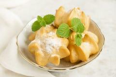Profiteroles avec de la crème et le sucre en poudre Photos stock