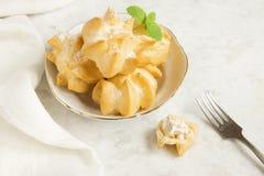 Profiteroles avec de la crème et le sucre en poudre Photo libre de droits