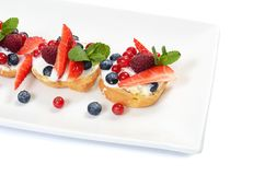 Profiteroles with berries currant , strawberries Royalty Free Stock Photography