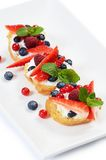 Profiteroles with berries currant , strawberries and blueberries Royalty Free Stock Photography