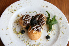 Profiteroles with berries on white plate Stock Photos