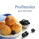 Profiteroles and blueberries over white with sample text Royalty Free Stock Photos