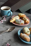 Profiteroles with butter cream and topping on the plate against grey background. Coffee break pause. Pastel shades. Stock Photos
