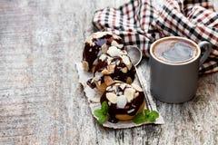 Profiteroles caseiros com amêndoas e xícara de café em de madeira foto de stock royalty free