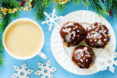 Profiteroles with chocolate icing and colored powder and coffee Stock Image