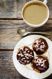 Profiteroles with chocolate icing and colored powder and coffee Royalty Free Stock Photography