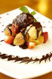 Profiteroles with chocolate sauce, strawberry and Royalty Free Stock Image