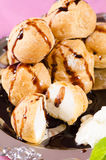 Profiteroles with chocolate syrup on table Stock Photos