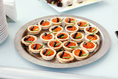 Profiteroles con el caviar rojo en el fondo blanco Partido de coctel Imagen de archivo