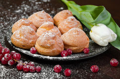 Profiteroles with cream on black plate, dark background Stock Images