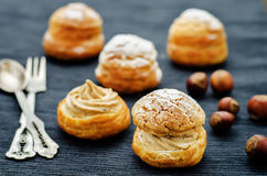 Profiteroles with cream with praline Stock Images