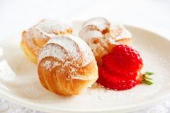 Profiteroles with cream and strawberries. Stock Photos