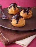 Profiteroles do chocolate fotos de stock