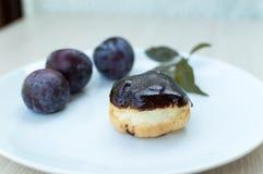 Profiteroles dolci con la glassa del cioccolato e della crema e prugne sulla a Fotografia Stock Libera da Diritti