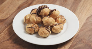 Profiteroles with fine dark chocolate on plate Stock Photo