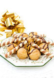 Profiteroles and golden ribbon. Celebrating food with delicious profiteroles and chocolate waffles. Isolated on white background royalty free stock photography