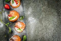 Profiteroles med den piskade kräm, jordgubbar och mintkaramellen arkivbild