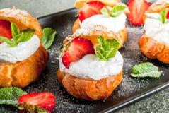 Profiteroles med den piskade kräm, jordgubbar och mintkaramellen arkivbilder